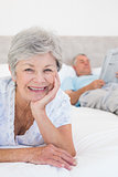 Smiling senior woman with man in bed