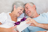 Senior couple exchanging gift box in bed
