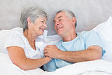 Senior couple holding hands in bed