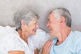 Smiling senior couple in bed