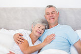 Senior man embracing woman in bed