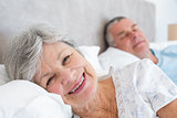 Senior woman lying on bed with man