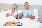 Happy senior couple having breakfast in bed