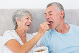 Loving senior woman feeding cereals to husband