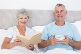 Senior couple with book and bowl in bed