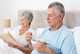 Senior couple with cereal bowl and book