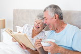 Senior couple reading book in bed
