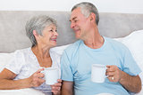 Senior couple with coffee cups in bed