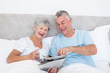 Senior couple reading newspaper in bed