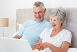 Senior couple laughing while using laptop in bed