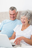 Senior couple using laptop computer in bed