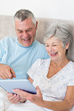 Senior couple using digital tablet in bed