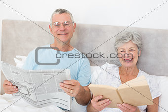 Senior couple holding newspaper and book in bed