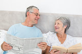 Senior couple with newspaper and book in bed