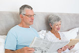 Senior couple with newspaper and book in house