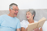 Senior woman showing book to husband in bed