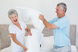 Senior couple having pillow fight in bed