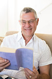 Senior man holding book on sofa