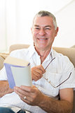 Senior man holding book and glasses