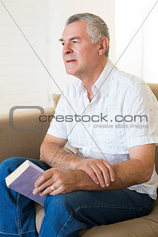 Thoughtful senior man holding book on sofa