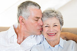 Senior man kissing wife on cheeks