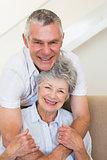Senior man embracing wife on sofa