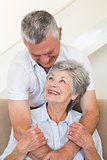 Senior man hugging wife sitting on sofa