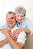Senior woman embracing husband in house