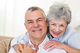 Senior woman embracing husband from behind