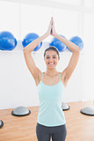 Beautiful woman with joined hands in fitness studio