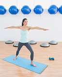 Sporty young woman stretching hands in fitness studio