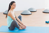 Smiling fit woman doing the butterfly stretch in exercise room