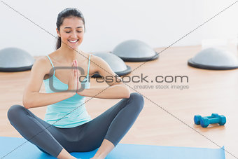 Beautiful sporty woman with joined hands in fitness studio