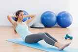 Determined woman doing sit ups in fitness studio