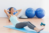 Smiling woman doing sit ups in fitness studio