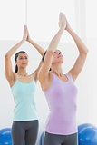 Women with joined hands in fitness studio