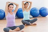 Two women stretching hands in fitness studio