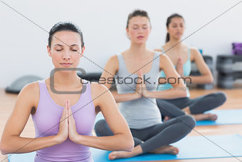 Women in Namaste position with eyes closed at fitness studio