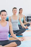 Women in lotus posture with eyes closed at fitness studio