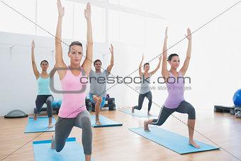 Class doing pilate exercises in fitness studio