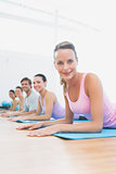 Portrait of fit class exercising at fitness studio