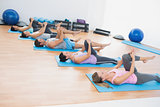 Sporty people stretching legs in fitness studio