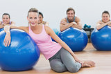 Instructor and class with exercise balls sitting at fitness studio