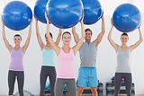 Fitness class holding up exercise balls at the fitness studio