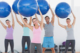 Fitness class holding up exercise balls at fitness studio
