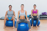 Sporty people sitting on exercise balls at gym