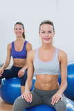 Sporty women sitting on exercise balls in gym