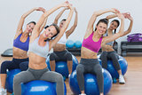 Sporty women stretching up hands on exercise balls at gym
