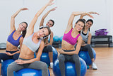 Sporty women stretching hands on exercise balls at gym