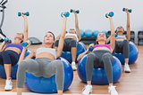 Fit class exercising with dumbbells on fitness balls